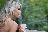 Blonde woman sits with cup on garden veranda