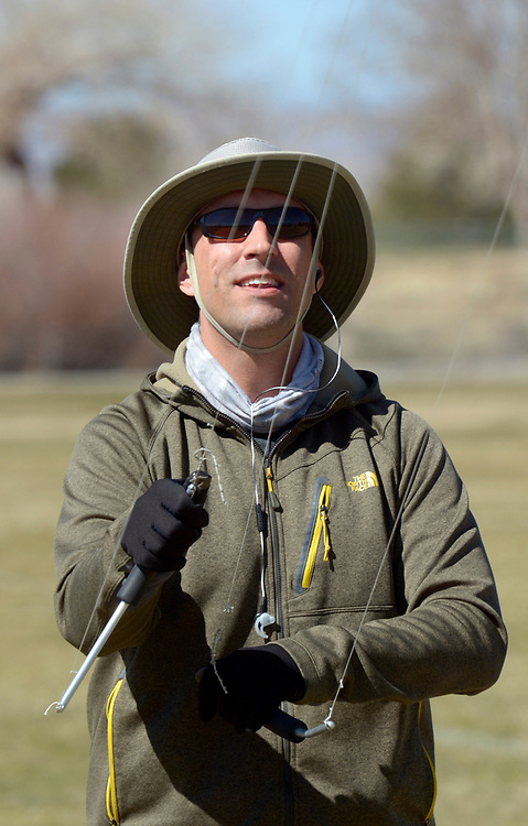 gbs030617b/ASEC -- David Costello of Albuquerque uses two handles and four strings to fly his Revolution kite in Arroyo Del Oso Park on Monday, March 6, 2017. The braided, fixed length, nylon strings control the sport kite which is made for high winds. The strings cost $60. One of his six revolution kites can fly in 25 to 30 mph sustained wind. (Greg Sorber/Albuquerque Journal)