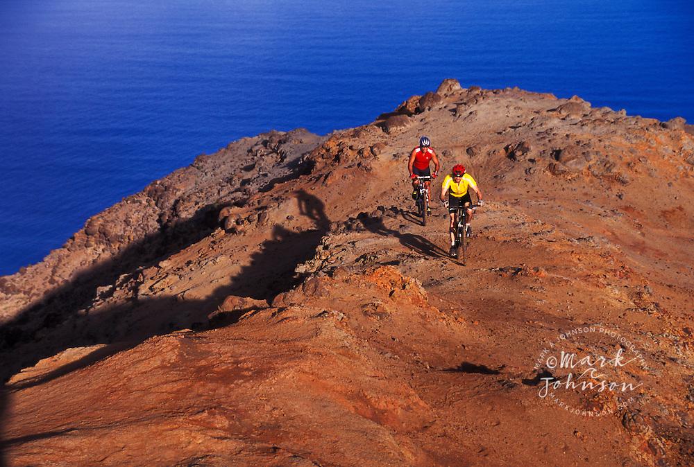 2 men mountain biking on a ridge above the Na Pali coast, Kauai, Hawaii