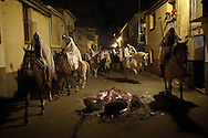 "Horsemen march next to a bonfire during the ""La Encamisa"" Festival on December 7,  2014 in Torrejoncillo, Extremadura region, Spain. ""La Encamisa"" is an ancient festival in honor of Immaculate Conception. Hundreds of horsemen wearing a white sheet gather outside the church in the main square. The procession starts when a banner with the image of Immaculate Conception is delivered to the horse rider steward and people cheer and shoot blanks. There are bonfires along the way where people gather to chat, eat traditional sweets and drink local wine. The origin of this tradition is unknown but it is believed the festival comes from a military event in which people from Torrejoncillo were involved. The war in Flanders in 1585, the Battle of Pavia or a legend of the siege suffered by city of Coria. (© Pablo Blazquez)"