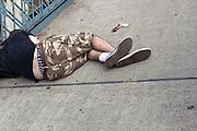 man asleep on the sidewalk of the Manhattan Bridge in New York