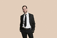 Portrait of a young businessman with hands in pockets over colored background