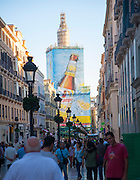 Busy shopping street Calle Marques de Larios, city centre Malaga, Spain large billboard beer advert