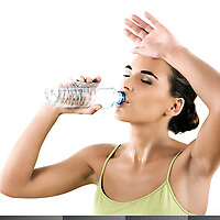 beautiful brunette  woman on white background drinking mineral water in a plastic bottle