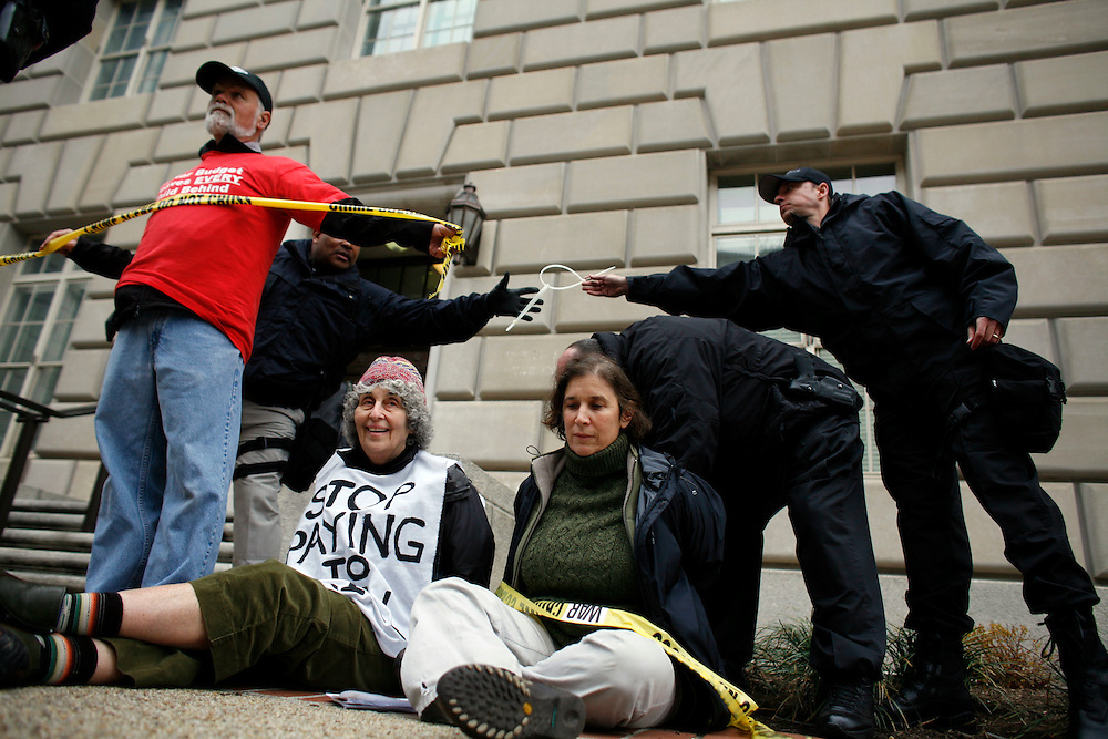 """Washington, Mar. 19, 2008 -Protesters are arrested in front of an entrance to the IRS headquarters in Washington on Wednesday, Mar. 19, 2008 in Washington.  The group is marking the 5th anniversary of the U.S. led invasion of Iraq with """"acts of civil disobedience."""""""