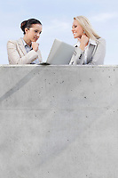 Low angle view of businesswomen looking at laptop while standing on terrace against sky