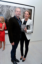 IAN & SAFFRON WACE at a private view of photographs by wildlife photographer David Yarrow included in his book 'Encounter' held at The Saatchi Gallery, Duke of York's HQ, King's Road, London on 13th November 2013.
