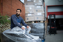 "© Licensed to London News Pictures. 07/05/2020. Salford, UK. Manager at Puro Medico SALAIMAAN MAJID (28) sits in front of remaining stock of masks stored outside the warehouse from where the PPE was stacked up when it was stolen . £166,000 (one hundred and sixty six thousand pounds) worth of protective masks , which were destined for the NHS and care homes , have been stolen from a warehouse overnight (6th-7th May 2020) in what Greater Manchester Police are describing as a "" targeted burglary "" . Thieves cut the shutters at the loading bay of Puro Medico - which specialises in importing PPE such as masks from China and hand sanitiser from Poland - and stole several pallets of stock , which was loaded on to vans over a two hour period . Photo credit: Joel Goodman/LNP"