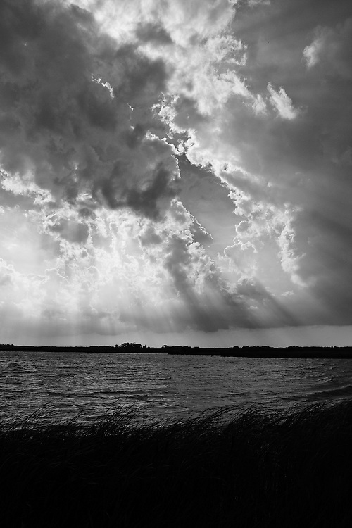 Black and white image of Back Bay just after a thunderstorm with the sun breaking through the clouds, Back Bay National Wildlife Refuge, Virginia Beach, Virginia.