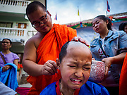 "03 APRIL 2018 - CHIANG MAI, THAILAND: A Shan boy reacts as a Buddhist monk shaves his hair before the Poy Sang Long ceremony at Wat Pa Pao in Chiang Mai. Poy Sang Long (""The Festival of the Crystal Sons"") is a ceremony that marks a rite of passage among the Buddhist Shan people in Myanmar and northern Thailand. Boys between seven and fourteen years of age are ordained as Buddhist novices during a three day ceremony. Before the ceremony starts the boys have their heads shaved.       PHOTO BY JACK KURTZ"