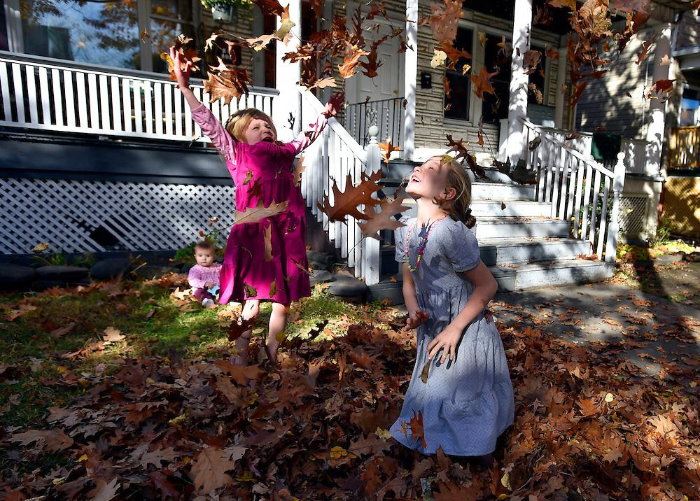 Sharita 3, and Diane 6, Longenecker play in fleshly raked leaves while their baby sister Rosalie looks on.