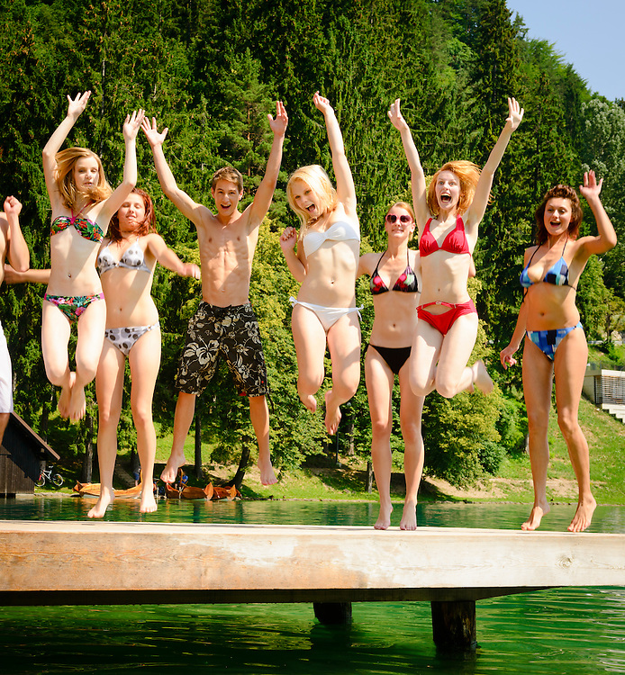 Teenagers on a summer vacation having fun together jumping on a jetty by a lake.