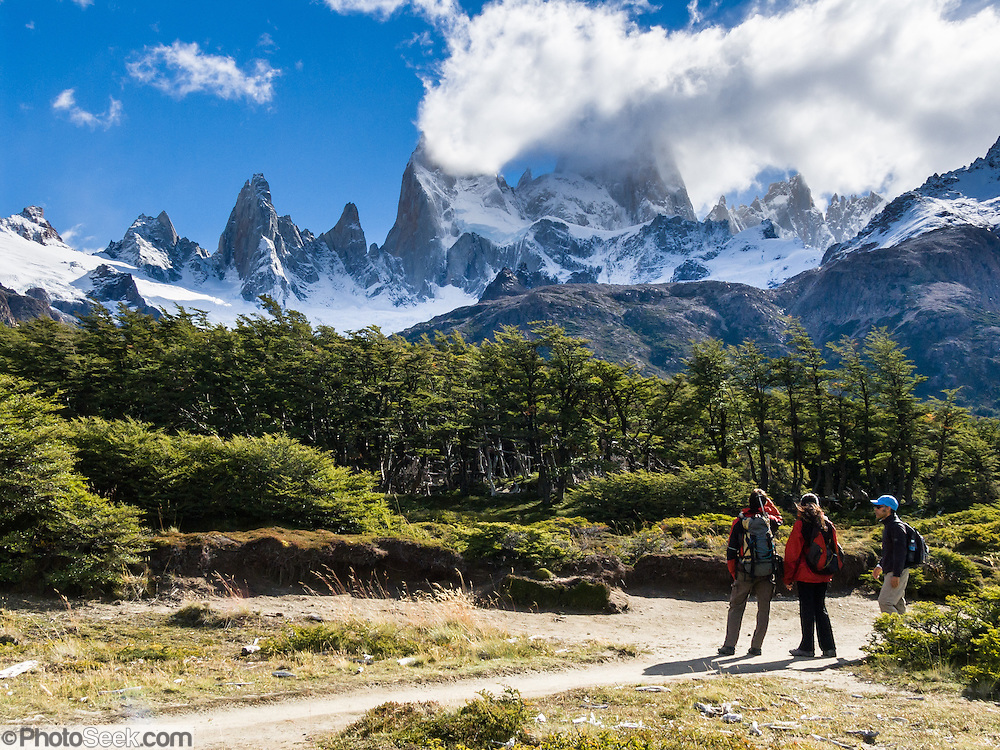 """Mount Fitz Roy (3405 meters or 11,170 feet) rises abruptly above native forest in the southern Andes mountains, near El Chaltén village, in Los Glaciares National Park, Argentina, South America. In 1877, explorer Perito Moreno named """"Cerro Fitz Roy"""" for Robert FitzRoy (no space before the capital R) who, as captain of the HMS Beagle, had travelled up the Santa Cruz River in 1834 and charted much of the Patagonian coast. First climbed in 1952 by French alpinists Lionel Terray and Guido Magnone, Mount Fitz Roy has very fickle weather and is one of the world's most challenging technical ascents. It is also called Cerro Chaltén, Cerro Fitz Roy, and Monte Fitz Roy (with a space before the R). Chaltén comes from a Tehuelche (Aonikenk) word meaning """"smoking mountain"""" (explained by frequent orographic clouds). Cerro is a Spanish word meaning hill. El Chaltén village was built in 1985 by Argentina to help secure the disputed border with Chile, and now tourism supports it, 220 km north of the larger town of El Calafate. The foot of South America is known as Patagonia, a name derived from coastal giants, Patagão or Patagoni, who were reported by Magellan's 1520s voyage circumnavigating the world and were actually Tehuelche native people who averaged 25 cm (or 10 inches) taller than the Spaniards. Mount Fitz Roy is the basis for the Patagonia company's clothing logo, after Yvon Chouinard's ascent and subsequent film in 1968."""
