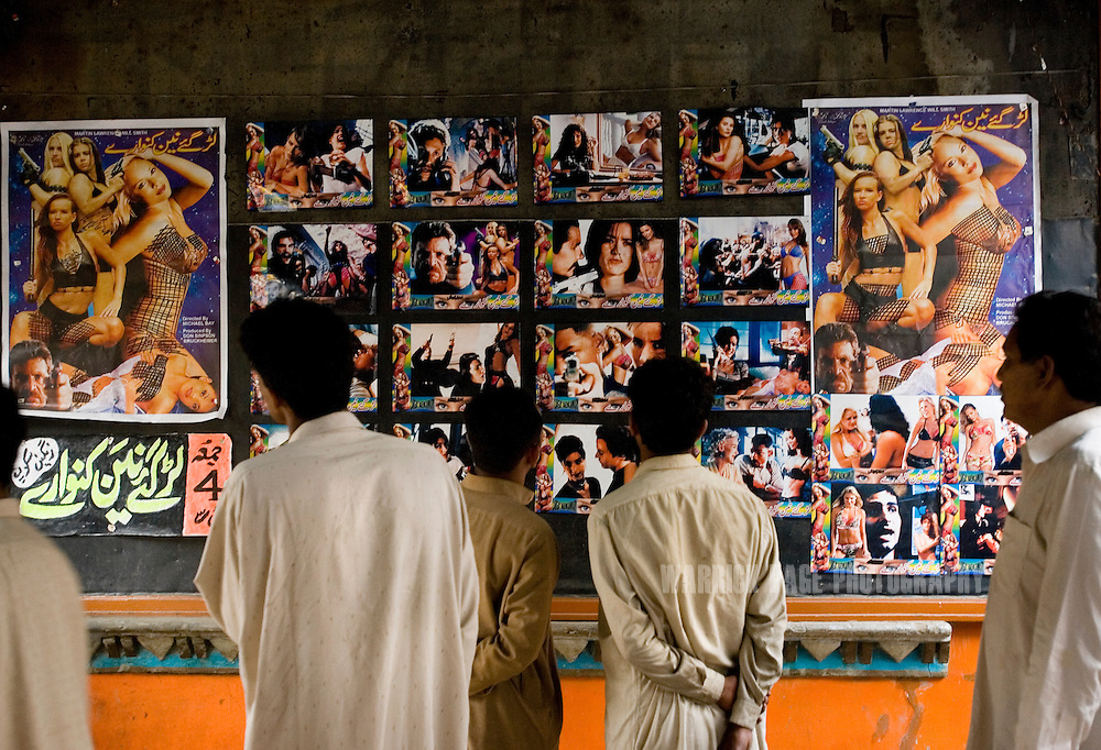 LAHORE, PAKISTAN - MAY 10: Patrons view soft-porn posters outside a Pashtoon cinema on Thursday, May 10, 2007, in Lahore, Pakistan. Certain theatres operating under the guise of showing feature productions, regularly cut to hardcore pornography 20-30 mins after beginning screening of a feature film. Sex and violence now dominate Pakistani cinema, enticing rural and working-class males, but driving family audiences from the theatres. As thawing relations between Pakistan and India lead them closer to regional stability, Pakistan's film industry takes another hit as Bollywood films dominate an already floundering institution, as the Pakistani government eases a 43-year-old ban on screening Indian films and audiences are drawn to their neighbours silver-screen theatrics. Once a thriving film industry in the chaotic and colourful city of Lahore, Pakistan's answer to Bollywood - Lollywood - is now a shadow of its former self. Two decades ago 11 studios averaged a collective 100+ films per year as cinemagoers filled more than 1000 theatres across the country. Today, only one functioning studio struggles to produce a single film for the country's 200 decaying theatres. (Photo by Warrick Page)