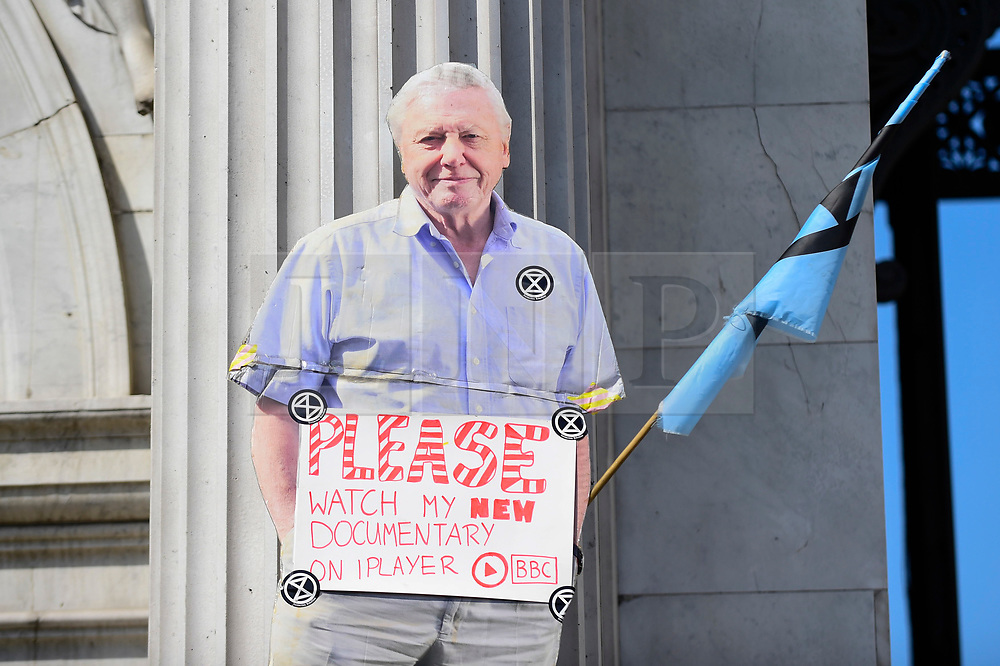 """© Licensed to London News Pictures. 22/04/2019. LONDON, UK. A cut out of broadcaster David Attenborough affixed to Marble Arch. Activists gather at Marble Arch during """"London: International Rebellion"""", on day eight of a protest organised by Extinction Rebellion.  Protesters are demanding that governments take action against climate change.  After police issued section 14 orders at the other protest sites of Oxford Circus, Waterloo Bridge and Parliament Square resulting in over 900 arrests, protesters have convened at the designated site of Marble Arch so that the protest can continue.  Photo credit: Stephen Chung/LNP"""