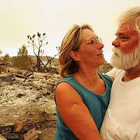 Crystal Chatham/The Desert Sun<br /> <br /> 07/13/2006 -- Joanne Kretschmer, 49, embraces her husband of 29 years Fred Kretschmer, 52, while sifting through the remains of their 3-bedroom home in Pioneertown on Wednesday afternoon. Fred, who is a carpenter, built their home piece by piece from 1981-83. He promised his wife he'd build a new home by Christmas - this time with a bigger bathroom.