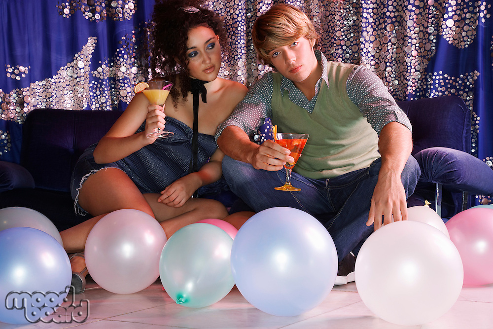 Teenagers drinking cocktails on sofa balloons on floor in front