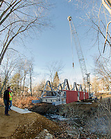 Mark Roberts operates the crane maneuvering the bridge into place with Ron Mitchell and Chris Clairmont ready to guide the placement on the Belmont Mill side of the river in Belmont Village Monday morning.  (Karen Bobotas/for the Laconia Daily Sun)