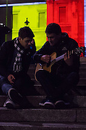 A man listens to his friend playing guitar as behind them the national gallery in Trafalgar Square is illuminated in the colours of the Belgian flag in a display of solidarity with Belgium following the terror attacks on March 22nd. Westminster, London<br /> Picture by Paul Davey/Focus Images Ltd +447966 016296<br /> 23/03/2016