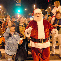 Santa Claus leads a Candlelight Walk from the California Heritage Museum lawn to the Shopping Cart Tree at Edgemar Courtyard during the Main Street Annual Holiday Festival on Saturday, December 4, 2010.