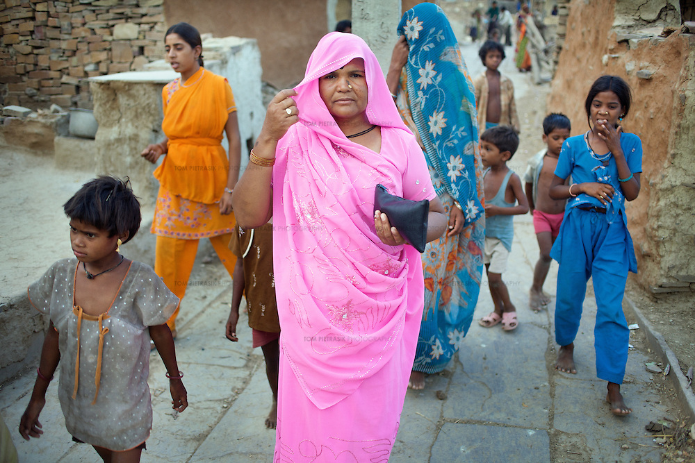 Dharkan 107.8 program-maker Ramvati Adivasi carries her minimal recording equipment through the Adivasi (tribal, or Scheduled Tribe) village of Patara, 20km from Shivpuri. Adivasi has recorded several programs and interviews informing women of government health services. Adivasi is is an ASHA (local female health advisor). She provides a free referral service to local women, keeping them in touch with government health services. Adivasi receives a fee from the government for every referral. This is one means by which the government and partners UNICEF are increasing the rate of institutional deliveries in Madhya Pradesh state. Adivasi has recorded several programs informing women of government health services. ..Shivpuri district in Madhya Pradesh suffers from poor health outcomes. Of particular concern is the high rate of maternal mortality. One of the Indian government's aims, with partners Unicef, is to encourage the population to adopt practices to improve sanitation and health practices. In an area made up of traditionally disadvantage groups and suffering low literacy rates, this can be a challenge. ..A survey found that radio was the most readily accessible media by the Shivpuri community with more than half saying they tuned in several times a day. ..Dharkan 107.8 FM will go on air in July. The station that will broadcast to 75 villages in a 15-kilometer radius reaching 170,000 people...Rather than preaching educational messages, the station, which is already producing pilot programs, uses humor and folk artists performing in the local language to entertain and inform their audiences. There is a major impact, especially on women, who are contributing their voices to such wide-ranging issues as caste discrimination, female feticide and women,A?o?s empowerment. ..Photo: Tom Pietrasik.Shivpuri, Madhya Pradeh. India.June 2009