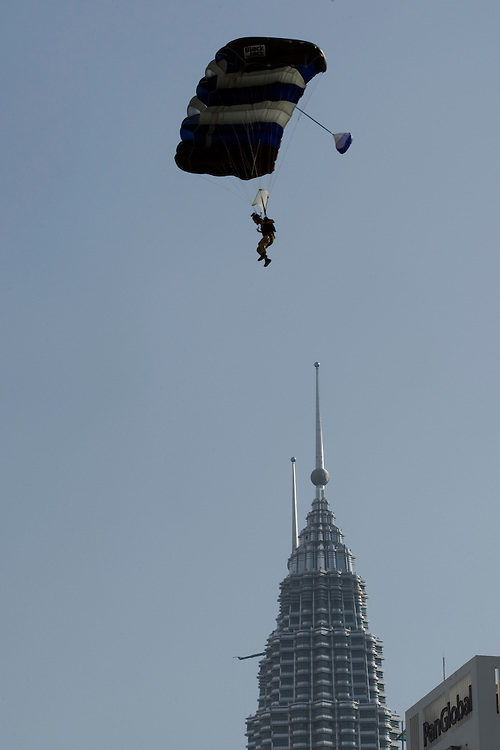 BASE jumper floats near the Malaysia's landmark, Petronas Towers during an attempt to set a new record in 24 hours in Kuala Lumpur, Malaysia 29 October 2008. Heavy rain has foiled an attempt to rewrite the world record for endurance BASE jumping in 24 hours at the 421-metre high KL Tower. The group, comprising jumpers from Canada, China, Denmark, Holland, India, Indonesia, Ireland, Italy, Malaysia, New Zealand, Norway, Russia, Singapore, and Turkey, managed 543 jumps, 33 short of the world record of 576 as per the Guinness Book of World Records.BASE is an acronym for Building, Antennae, Span, Earth, and thus represents the fixed-objects from which BASE jumps are made.The jumper must allow a free fall of about three seconds to clear the tower-head section before deploying their chute.From a height of 300 metres, without a parachute, it takes only 10 - 12 seconds to reach the ground.