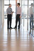 Two Businessmen Talking in Corridor.