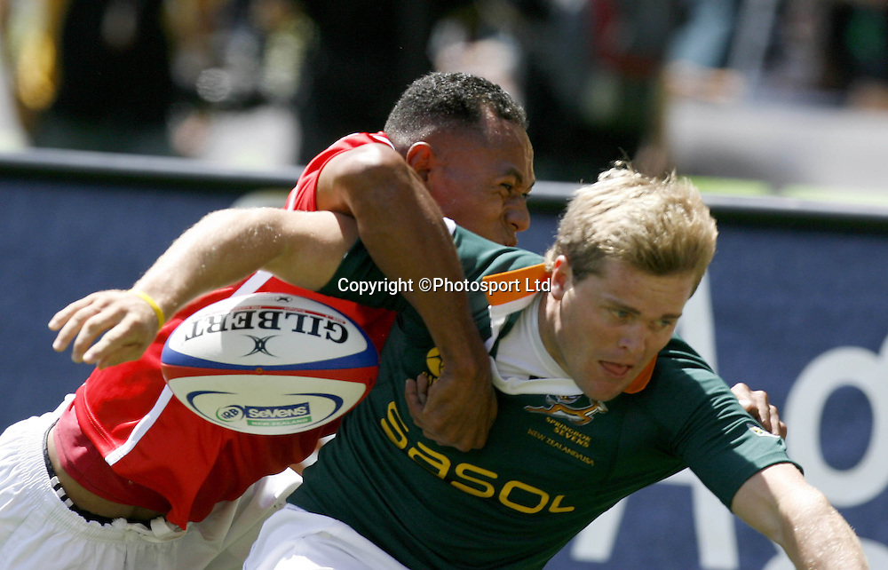 South Africa's Stefan Basson (R) loses the ball in the tackle of Tonga's Sitikeni Katoa in a first round match in the International sevens rugby tournament at Westpac Stadium in Wellington, February 3, 2006.  PHOTO  Anthony Phelps/PHOTOSPORT