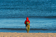A winter fisherman waits patiently on the beach after casting his line