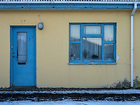 Yellow house with blue door and window. Vestmannaeyjar islands, Iceland.