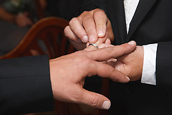 Two men at their Civil Ceremony, putting on a ring.