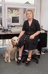 Woman with visual impairment and guide dog in office,