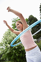 Girl in backyard playing with hula hoop