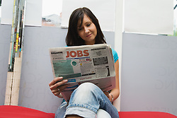 Czech woman looking in the job section of the newspaper for work,