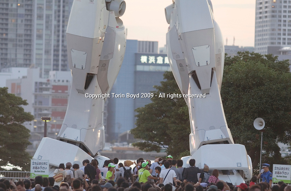 "This is the 59-foot-tall (18-meters) Gundam robot constructed in Tokyo to celebrate the 30th anniversary of the original Gundam character created by Yoshiyuki Tomino and Sunrise studios in 1979. This was an animation TV series called Mobile Suit Gundam, but since then the Gundam character has grown into a more than $500 million (50 Billion JPY) trademark owned by NAMCO BANDAI Holdings Inc. of Japan. The giant life size Gundam robot located in Shiokaze Park in Tokyo's Odaiba waterfront district is an event officially called ""Green Tokyo Gundam Project"". The statue, a 1/1 scale model of the RX78 Gundam animation robot can emit lights, mist, and rotate its head. This free event was opened to the public on July 10, 2009 and will end on August 31, 2009. After which the statue will be dismantled in early September. With the event winding down, attendance has been at a peak with tens of thousands visiting daily. The organizers have predicted over 1.5 million people will have visited the robot by the time the event ends."
