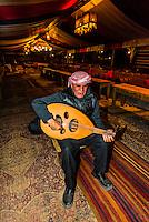 Bedouin man playing an oud (a type of lute), Captain's Desert Camp, Arabian Desert, Wadi Rum, Jordan.