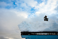 JEROME A. POLLOS/Press..Cory Sturgis takes a break from shoveling snow off of his father's garage Friday in Coeur d'Alene. Clearing snow off of rooftops has become a lucrative business for those with the ability to take on the work.