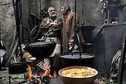 Scene from a street market in the Middle Ages with 2 men chatting behind the cooking pots at a food stall. Image taken from the filming of 'Paris la ville a remonter le temps' written by Carlo de Boutiny and Alain Zenou, directed by Xavier Lefebvre, a Gedeon Programmes production. Picture by Manuel Cohen