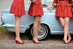 © Licensed to London News Pictures. 17/09/2011. GOODWOOD, UK. Drivers from women only drivers cab firm wait near their car. The Goodwood Revival at Goodwood in West Sussex today (17 September 2011). The revival is the world's largest historic motor race meeting, which relieves the 'glorious' days of the race circuit. Competitors and enthusiasts all dress in period fashion to enhance the experience. Photo credit : Stephen Simpson/LNP