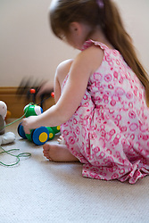 Little girl playing with her toys,
