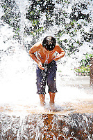 Boy playing in a water sprinkler.