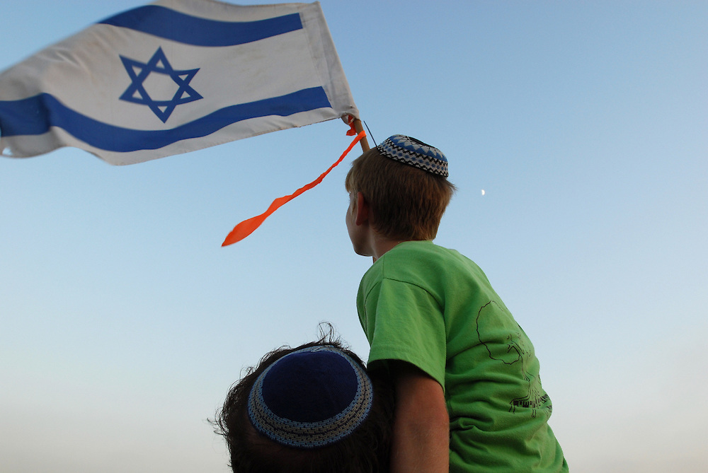 An Israeli settler child carries an Israeli flag in the illegal outpost of Givat Tzuria near the Jewish settlement of Avnei Hefetz, located East of the West Bank Palestinian city of Tulkarem, July 28, 2009.