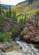 Hike through yellow aspen fall colors to Booth Creek Falls (4.3 miles / 1400 ft gain) on Booth Lake Trail #1885, near Vail, in Colorado, USA. This image was stitched from multiple overlapping photos.