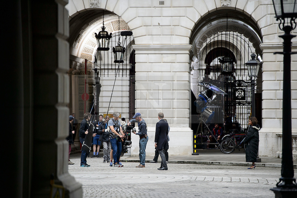 "© Licensed to London News Pictures. 30/05/2015. London, UK. Filming for the new James Bond film ""Spector"" with Daniel Craig (centre) and Naomie Harris (right) at the courtyard of the UK Government Treasury building in Westminster, London . Photo credit: Ben Cawthra/LNP"