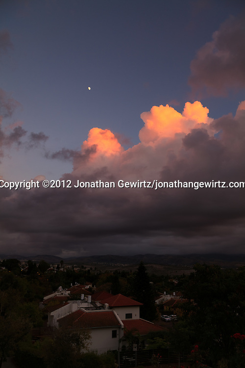 The last rays of the setting sun illuminate clouds over hills and houses in the Macabbim section of the city of Modi'in, central Israel. WATERMARKS WILL NOT APPEAR ON PRINTS OR LICENSED IMAGES.
