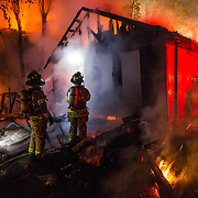 Firefighters battle a two-house blaze on University Avenue in Edmonton early Friday morning. The cause of the fire, which spread from one house to the next, is not yet known. Jesse Winter Photo.