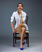 Studio fashion photo of seated model in short skirt with legs intertwined. Fashion photo by Gerard Harrison, Image Theory Photoworks. Model Elodie Tusac.