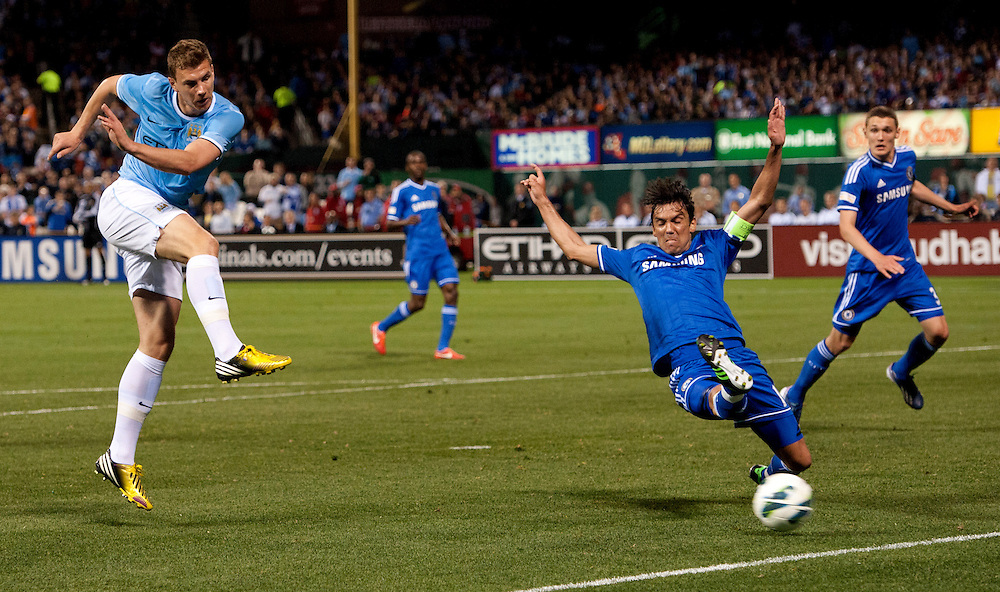 Manchester City's Edin Dzeko 10 shoots on goal as Chelsea's Paulo Ferreira 19 attempts to block him at Busch Stadium in St. Louis.