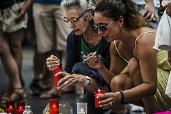 August 19, 2017 - Barcelona, Catalonia, Spain - Mourners place a candle at a makeshift memorial in Las Ramblas where a van ran a 550 meter long jihadist terror trip. Thirteen people were killed and almost 80 wounded, 15 seriously, when the van tore through the crowd (Credit Image: © Matthias Oesterle via ZUMA Wire)