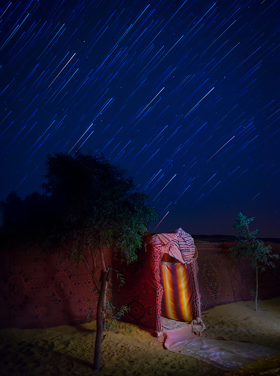 MEKNES - TAFILALET, MOROCCO - CIRCA APRIL 2017: Star trails over a Berber camp in the Sahara Desert